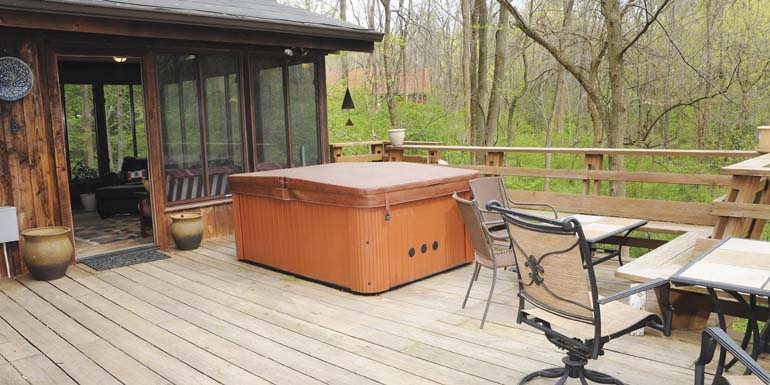 Hot Tub In The Woods - A large deck in the woods with a hot tub outside the lanai.