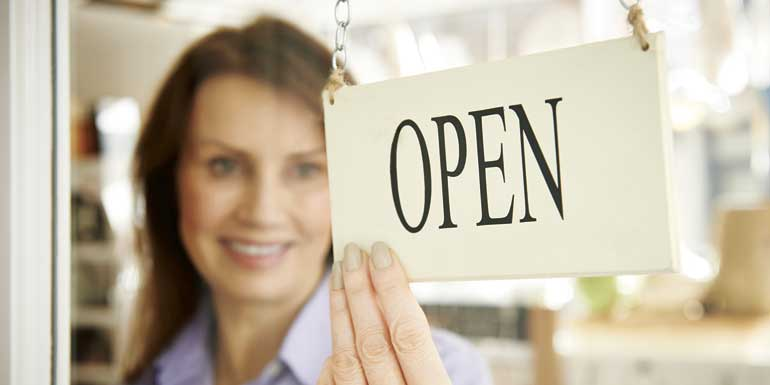 bigstock-store-owner-turning-open-sign-84316688