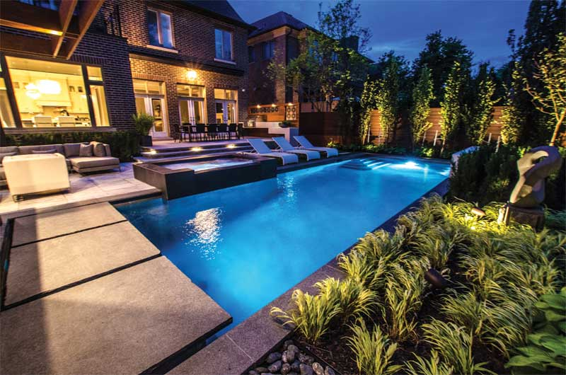 Backyard landscape, pool, and spa illuminated