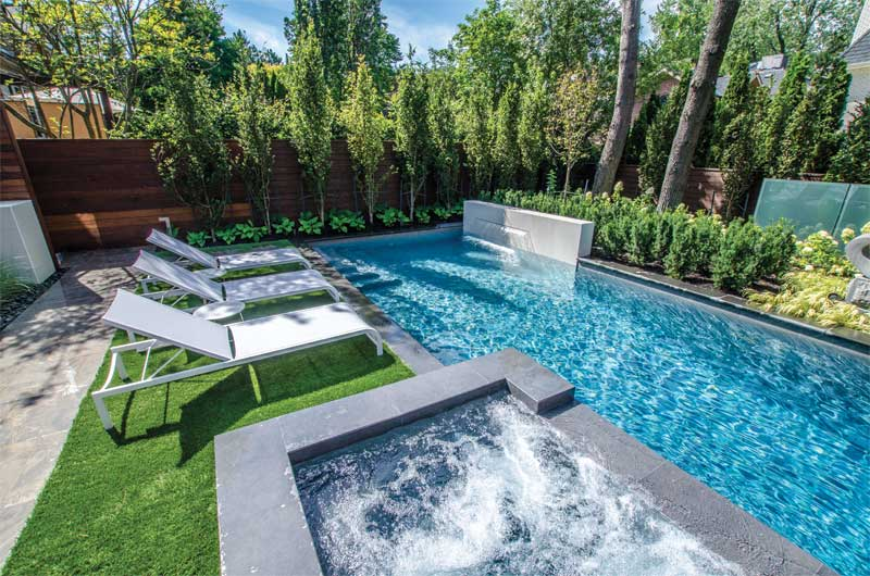 The pool includes a raised water feature and raised, attached concrete hot tub.