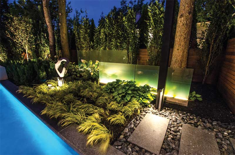 Frosted glass panels in the garden are illuminated with strip lights, which seem to glow.