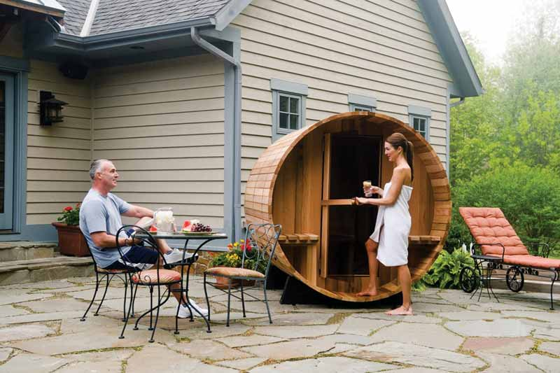 Woman entering a sauna in residential backyard.