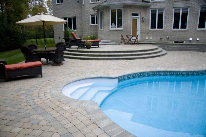 Poolside interlock concrete paver patio and raised terrace.