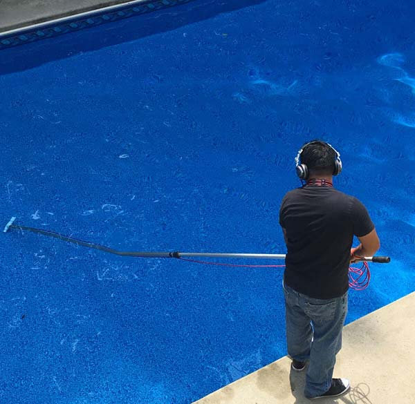 This technician is using a floor probe to perform a leak detection job on a vinyl-lined pool.