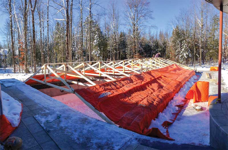 This temporary construction tent is custom framed with wood trusses and covered with insulated construction blankets.