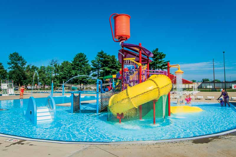 The splash pad is equipped with water-dumping amenities and spray features, which included a water tower, splash umbrella, and misting water wickets.