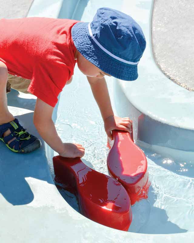 A discovery zone, featuring gentle spray textures, fascinating weirs, and meandering streams, provides a calm space for thoughtful play.