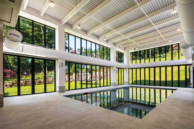 The unique 232-m2 (2500-sf), two-storey rectangular pool enclosure features  6.4-m (21-ft) high glass on three sides.