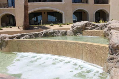 Multiple visual elements help accentuate the structure's overall design—cascading rock water features spray and aerate the water, which simultaneously help with the circulation and flow.