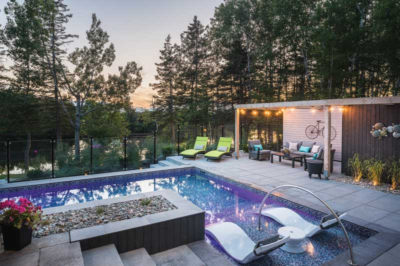 The client asked for a fenced pool and preferred a rectangular design that offered an in-pool lounge area. They also wanted a firepit and grassy area for the kids to play soccer.